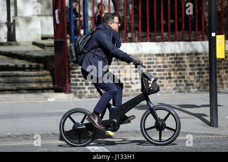 Business man on a fold up Go Cycle trendy bicycle  Gocycle G3 Folding Electric Bike with Base Pack - Matt Black - Stock Photo