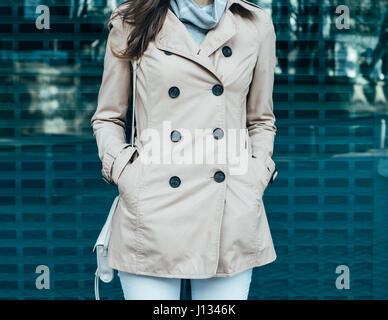 Clothing details: woman in jeans and a beige coat outdoors, close-up - Stock Photo