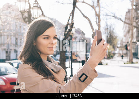 Young brunette woman in a beige coat takes pictures of herself on a smart phone in the city in the spring - Stock Photo