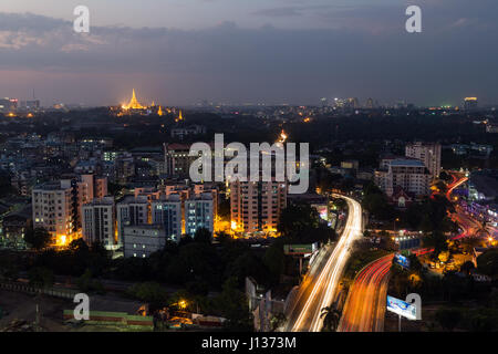 View of Yangon, Myanmar, from above in the evening. Lit Shwedagon Pagoda is in the distant. - Stock Photo