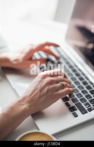Close-up picture of woman's hands typing a message on her laptop during lunch. - Stock Photo
