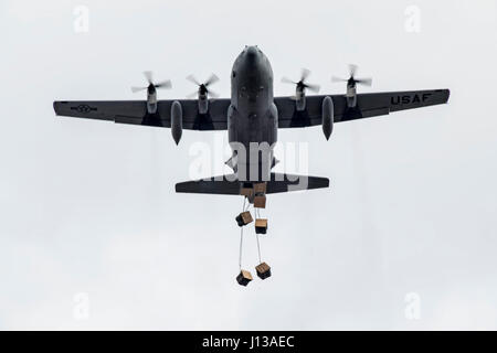 Airmen inside a C-130H Hercules assigned to the 36th Airlift Squadron drops containerized delivery system bundles - Stock Photo