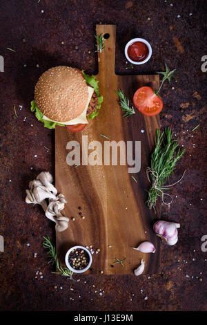 Fresh tasty burger and ingredients on wooden board. Restaurant menu frame, mock up. Top view, copy space. Beef. - Stock Photo