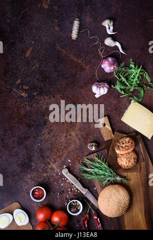 Fresh homemade burger on dark serving board with beef, tomatoes, cheese and eggs over dark background. Top view, - Stock Photo