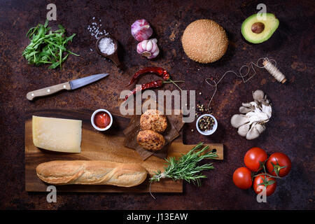 Fresh homemade sandwich on dark serving board with vegetables, cheese, salt and herbs over dark background. Top - Stock Photo