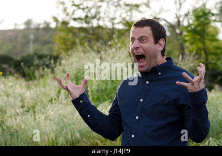 Man screaming in anger with hands out and mouth wide open - Stock Photo