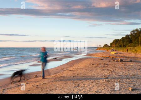 A woman walks a dog along Boiler Beach on Lake Huron, Ontario, Canada. Near the town of Kincardine - Stock Photo
