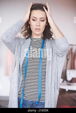 Confident clothing designer in her showroom - Stock Photo