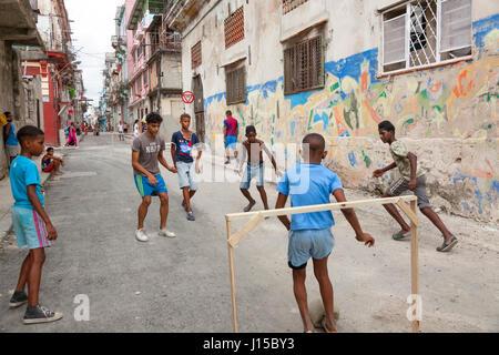 Cuban children playing soccer or football in the street in Havana, Cuba. - Stock Photo