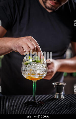 Barman is decorating a cocktail with a mint leaf - Stock Photo