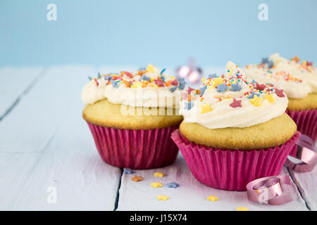Cup cakes on blue background - Stock Photo