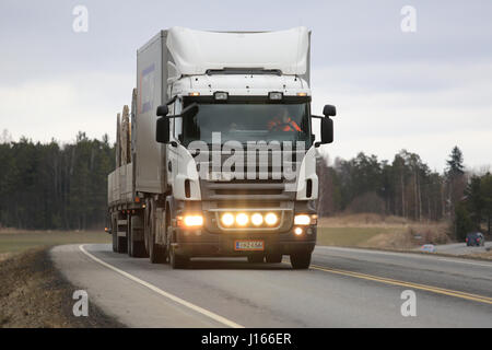 SALO, FINLAND - MARCH 24, 2016: White Scania truck and combination trailer moves along highway in South of Finland. - Stock Photo