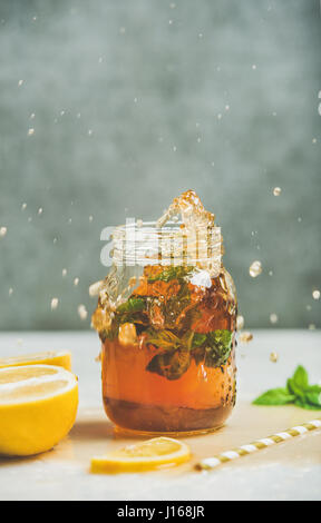 Summer cold Iced tea with lemon and herbs - Stock Photo