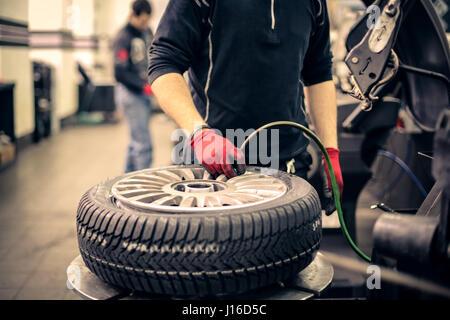 Mechanic man working on tire - Stock Photo