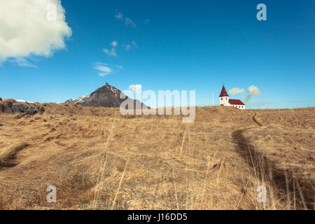 A white church sits on a hill in a golden field opposite a mountain. Hellnar, Snæfellsnes (Snaefellsnes) peninsula, - Stock Photo