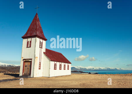 A white hilltop church sits in a golden field with views of the sea in Hellnar, Snæfellsnes (Snaefellsnes) peninsula - Stock Photo