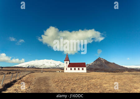 A cloud looms above the white church in Hellnar, Snæfellsnes peninsula in western Iceland - Stock Photo