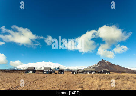 Black houses in a golden field, Hellnar, Snaefellsnes peninsula, western Iceland - Stock Photo