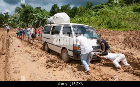 Tourists Looking At Local People Pushing Mini Bus Stuck Out Of The Mud In El Nido, Palawan - Stock Photo