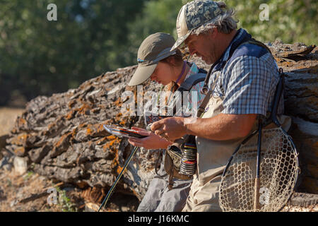 A Man And Woman Choosing A Fly From Fly Box While Fishing On Big Wood River In Ketchum, Idaho - Stock Photo