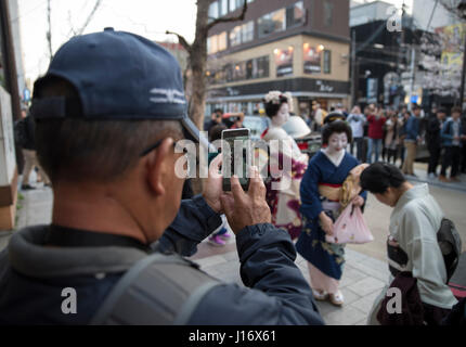 Man uses phone to photograph Geisha and Maiko ( trainee geisha )  waiting for taxi on Kiyamachi-dori street in Higashiyama - Stock Photo