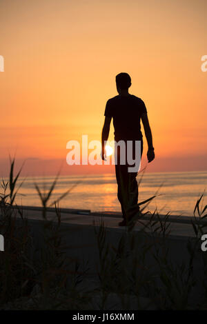 Full length silhouette of a male figure walking on the beach at sunset - Stock Photo