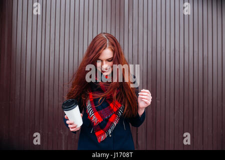 Beautiful happy young woman holding a paper cup and drinking coffee. Cheerful woman with red long hair in the street - Stock Photo