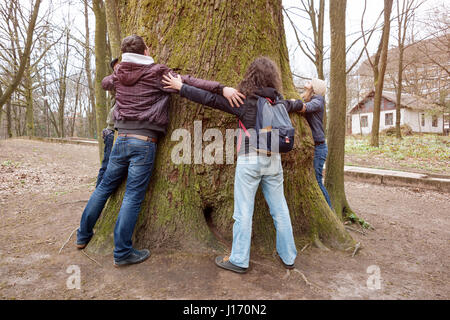 Group of friends hugging giant tree trunk and holding hands during hiking excursion. Tree hugging, tourism, ecology, - Stock Photo