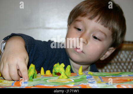 Little boy playing with playdough - Stock Photo