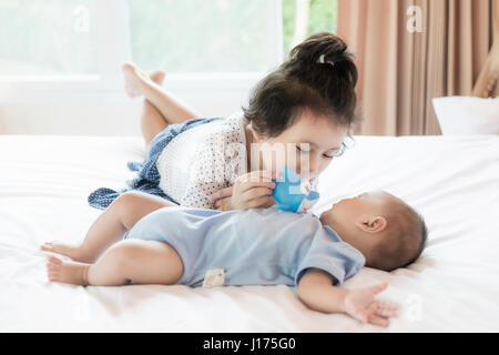 Asian baby brother and toddler sister playing fish doll in bedroom. Happy family. - Stock Photo