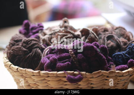 close up of wicker basket with different types of wool and fabric - Stock Photo