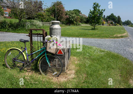 A decorative bicycle with a flower basket leaning up against a fresh milk churn at a farm in Herefordshire, Britain - Stock Photo