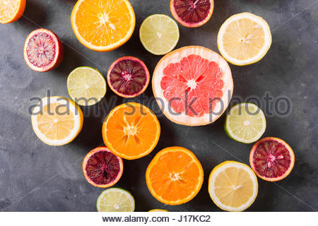 Different citrus fruit on gray concrete table. Whole and sliced fruit. Food background. Healthy eating and diet. - Stock Photo