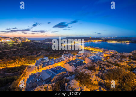 Il-Mellieha, Malta - Beautiful panoramic skyline view of Mellieha bay after sunset with blue sky and clouds - Stock Photo