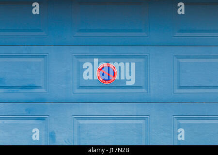 blue garage door with panel in French 'Please do not park Car exit' - Stock Photo