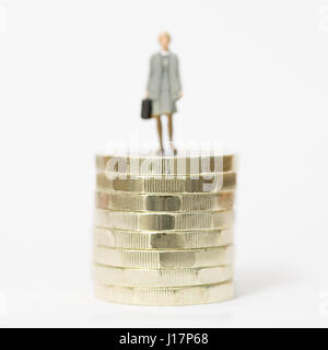 Close up/macro model stock photo depicting female wage worker on stack of new British pound coins.