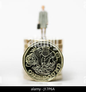 Close up/macro model stock photo depicting female wage worker on stack of new British pound coins. - Stock Photo