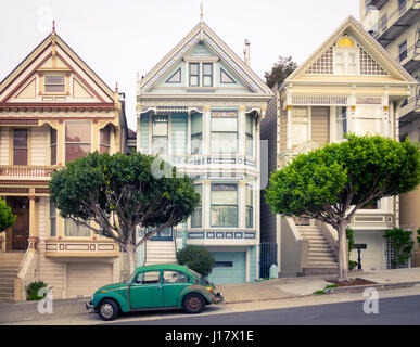 A green Volkswagen Beetle parked in front of the 'Painted Ladies' row of Victorian Houses on Steiner Street (at - Stock Photo