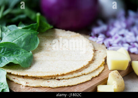 Corn tortillas surrounded by spinach, onions, and potatoes.  Ingredients for making vegan tacos. - Stock Photo
