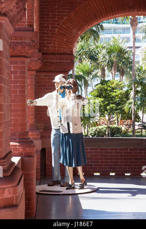 Statue called 'A Little to The Right' by artist Seward Johnson depicts a life-size, realistic couple using binoculars. - Stock Photo