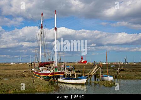 Boats moored on saltmarsh creek at Tollesbury, Essex, England UK - Stock Photo