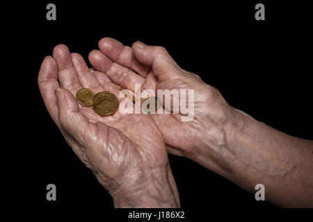 Senior woman hands holding some euro coins. Pension, poverty, social problems and senility theme. Isolated on black, - Stock Photo
