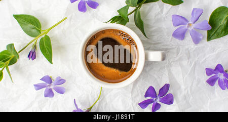 Cup of coffee and purple spring flowers on bed sheets - Stock Photo