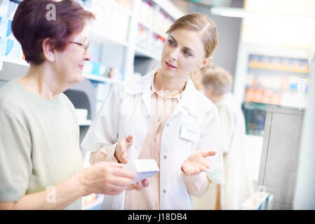 Customer discussing product with pharmacist - Stock Photo