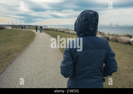 Lonely hooded female person from behind standing at seashore and looking into distance on a cold winter day, concept - Stock Photo