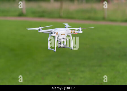 OLDENZAAL, NETHERLANDS - JUNE 19, 2016: DJI Phantom drone with camera attached flying low above the grass - Stock Photo