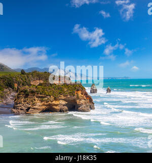 A view towards the Three Sisters at high tide, at the mouth of the Tongaporutu River, Taranaki Region, New Zealand. - Stock Photo