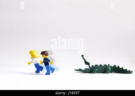 Male and female lego couple running scared from an alligator - Stock Photo
