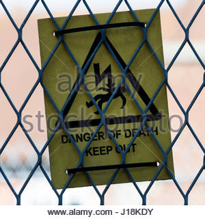 Close-up of a 'Danger Of Death - Keep Out' electricity sign a chain link fence in Blandford Forum, Dorset, England, - Stock Photo