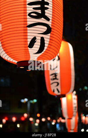 Japanese lanterns in Tokyo lit up orange in close-up against a black sky - Stock Photo